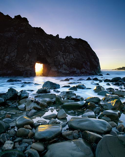 Sunlight Filtering Through Mountain Along A Beach